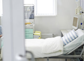 Empty bed in ward and senior woman sitting near by